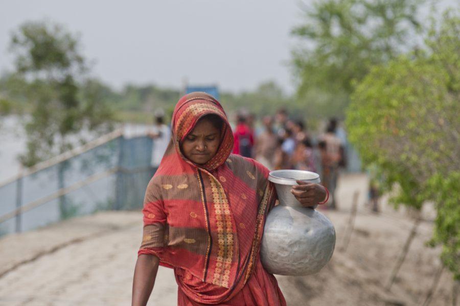 Rafiqul Islam/IPS | En kvinna som bor vid Bangladeshs kust bär hem dricksvatten.