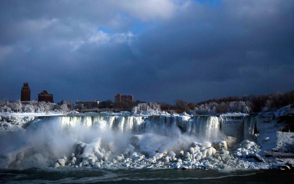 AP/TT | Vinterkylan får vattnet i fallen att frysa till is på sin väg nedför Niagarafloden.