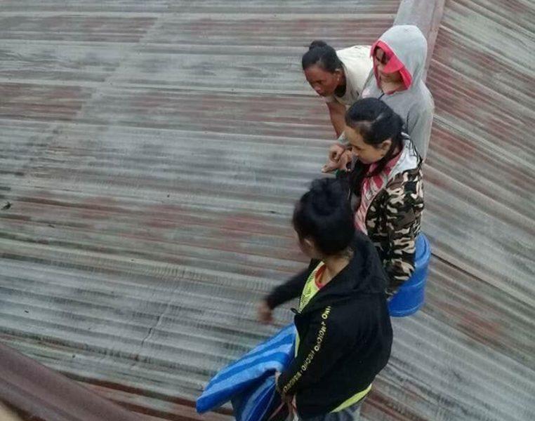 Lao National Television/AP/TT  Boende har sökt sig upp på tak för att komma undan flodvattnet som översvämmat byn.
