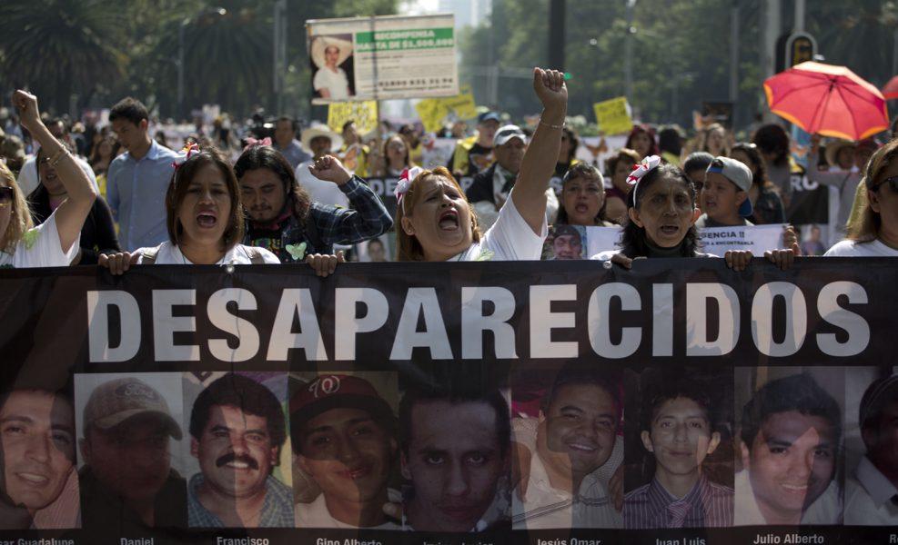 Kvinnor bär en banderoll med bilder på försvunna personer i samband med en demonstration på mors dag i Mexikos huvudstad Mexico City i våras.