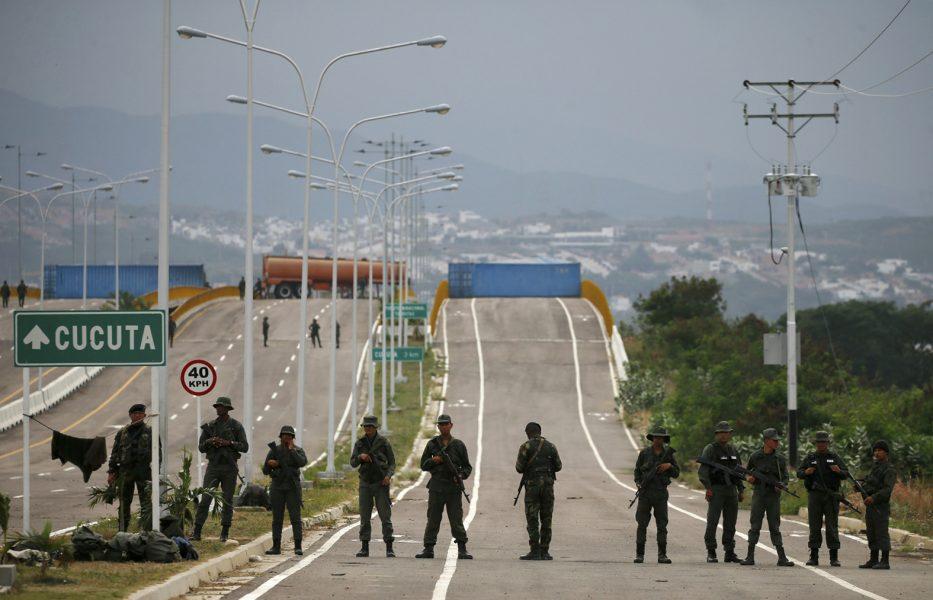 Venezuelanska soldater framför ett tankbilssläp och två stora containrar som spärrar av gränsbron över floden Táchira mellan Venezuela och Colombia.
