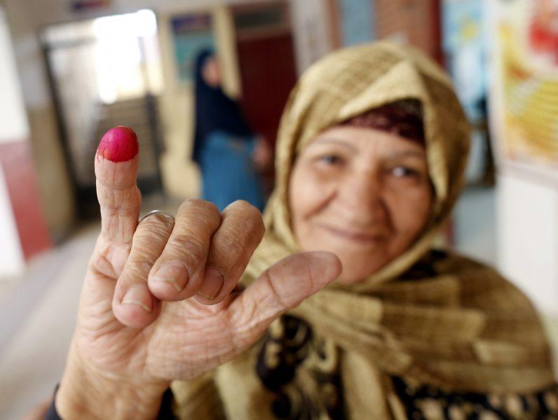 En kvinna visar upp sitt röda finger efter att ha röstat.