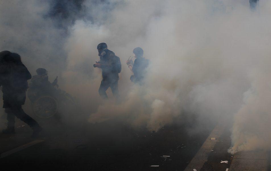 Aktivister flydde från tårgas under en förstamajdemonstration i Paris.