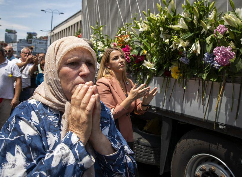 Kvinnor visar sin respekt inför de kistor som bilen som åker genom Sarajevo bär på: 33 män och offer i massakern Srebrenica har identifierats det senaste året.