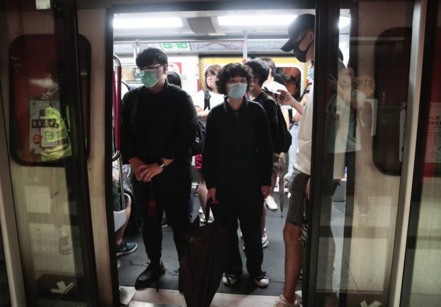 Demonstranter hindrar tågdörrar att stängas under måndagsmorgonen.