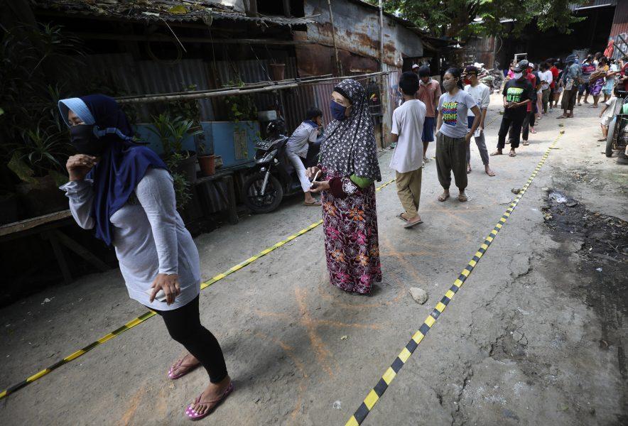 Fattiga indoneser håller avståndet när de köar för mat i ett slumområde i Jakarta.