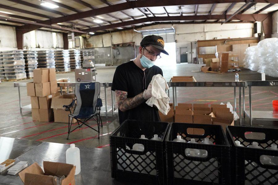 En man torkar av en flaska med handsprit vid en produktionsanläggning i Texas.