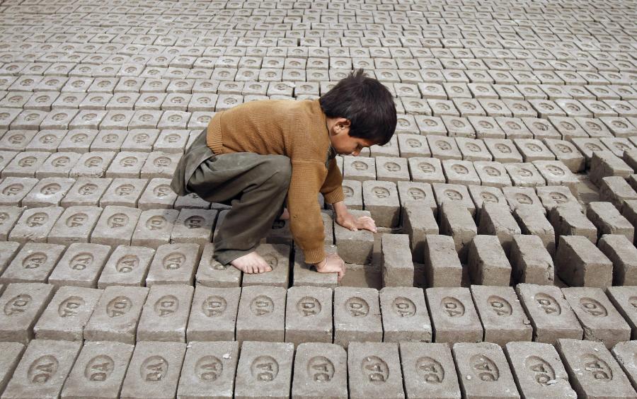 Ett barn i arbete på en tegelfabrik i Afghanistan.