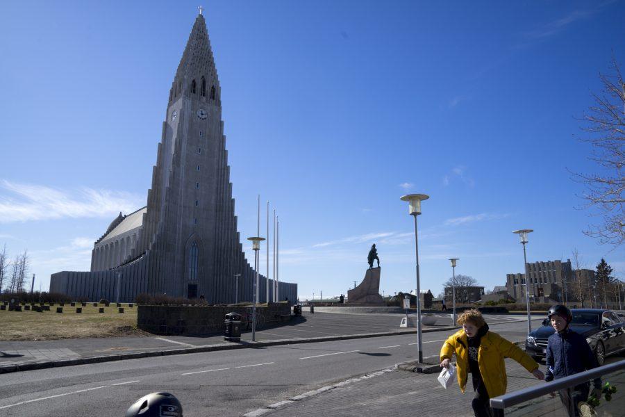 Två pojkar passerar ett tomt torg framför Hallgrímskirkja i Reykjavik i slutet av april, då landet meddelade lättnader i coronarestriktionerna.