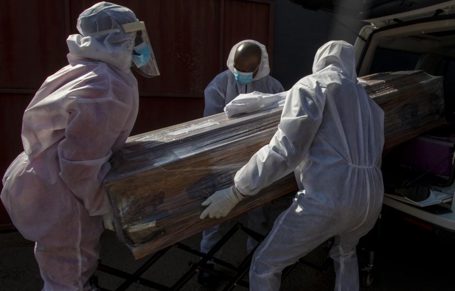 Anställda i skyddskläder bär en kista med en kvinna som dog av coronaviruset i tisdags, 21 juli.