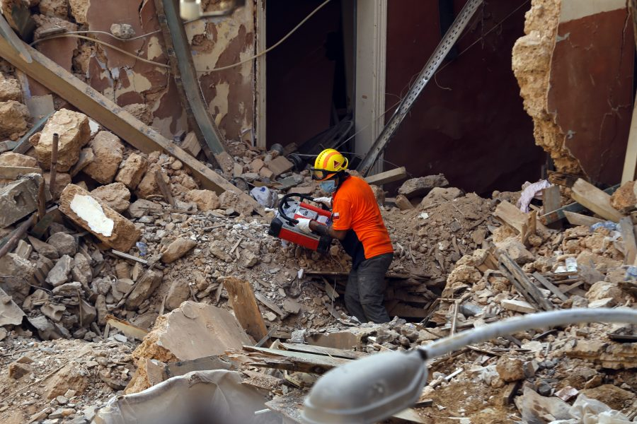 En chilensk räddningsarbetare letar efter livstecken i rasmassorna i Beirut.