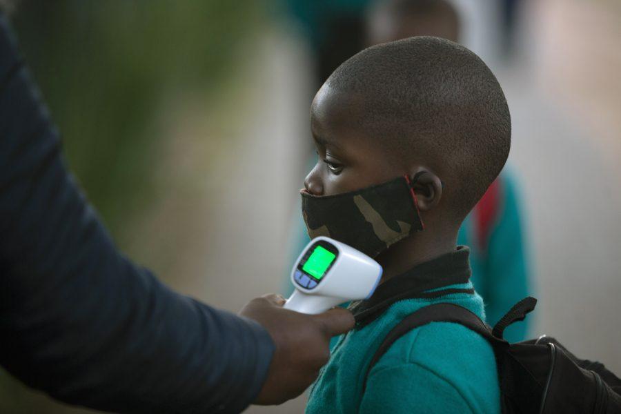 En skolelev får sin temperatur mätt i en skola i Johannesburg, Sydafrika.
