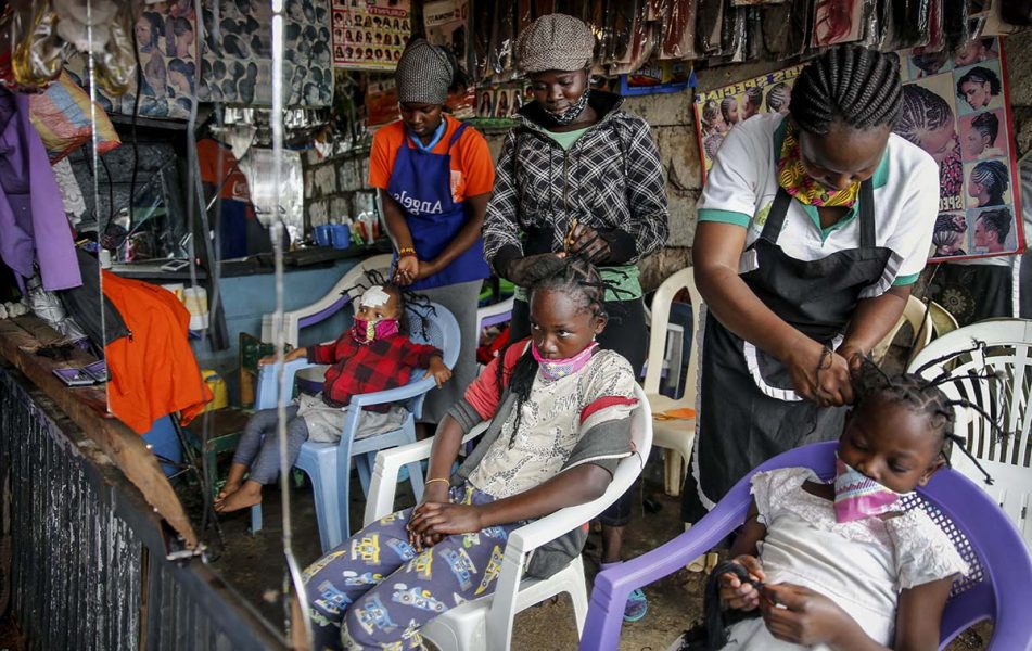 Smitttspridningen av Covid-19 och andra virus kan inte stoppas så länge fattiga tvingas ut och jobba för att överleva. Därför föreslår FN nu basinkomst. På bilden: Gettrueth Ambio, Jane Mbone, och Hamida Bashir, får håret stylat i samma form som nya coronaviruset, på salong Mama Brayo Beauty Salon i Kiberas slum slum i Nairobi, Kenya. Foto: Brian Inganga/AP/TT