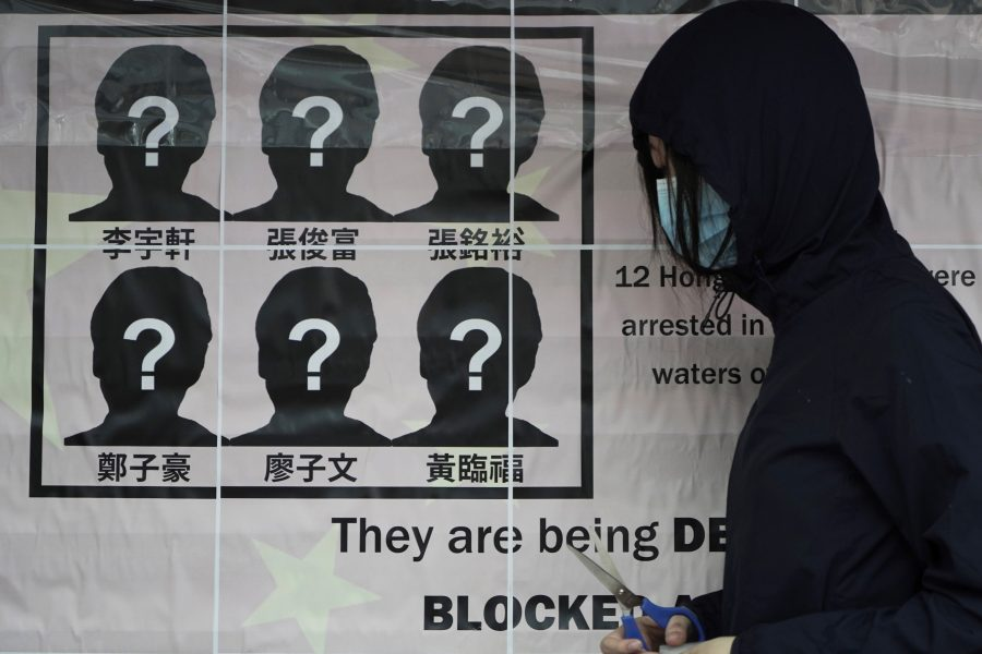 En universitetsstudent sätter upp en affisch som kräver att tolv aktivister som försökt fly från Hongkong släpps av Kinas myndigheter.