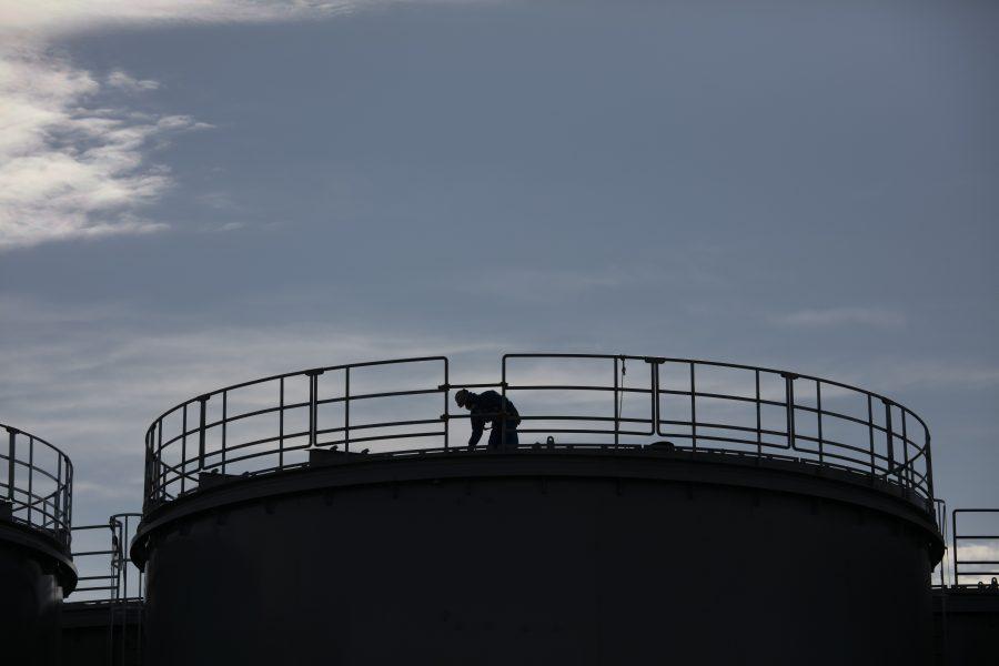En arbetare ovanpå en nybyggd vattentank vid kraftverket Fukushima Daiishi tidigare i år.