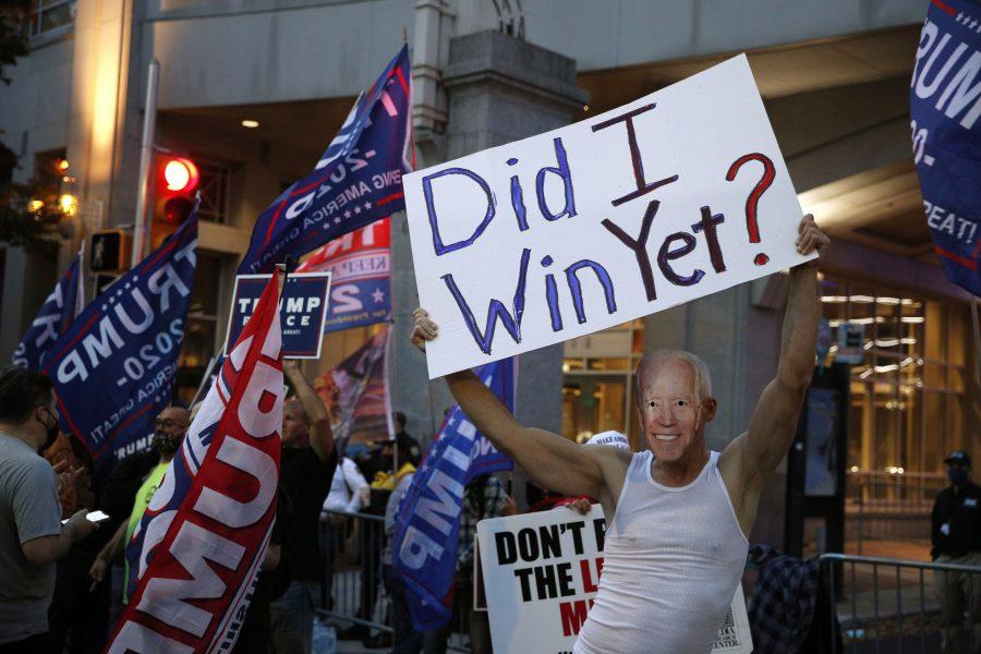 En Trumpanhängare bär en Joe Biden-mask utanför Pennsylvania Convention Center där rösträkning pågår.