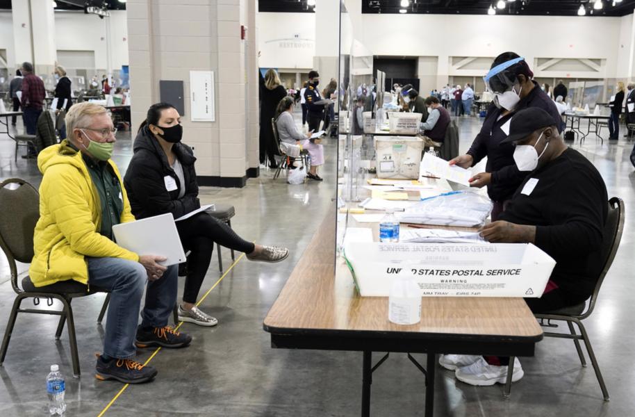 Valarbetare räknar om rösterna medan observatörer följer förloppet i Milwaukee, Wisconsin.