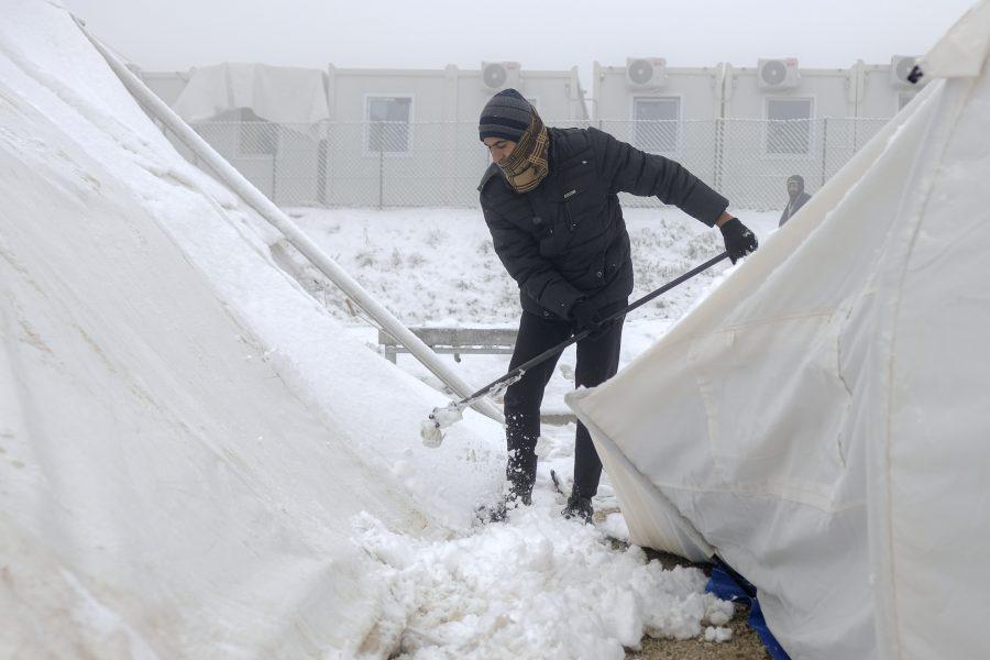 En av migranterna i det tillfälliga Lipalägret skyfflar bort snö från ett av de provisoriska tälten.