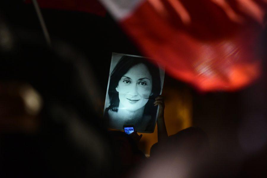 En demonstrant håller upp en bild på den mördare reportern Daphne Caruana Galizia vid en demonstration 2019.