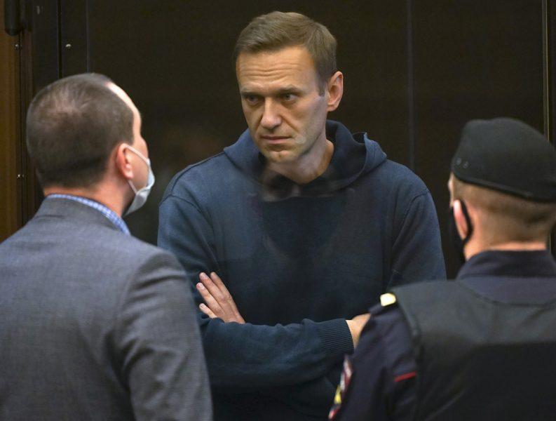 Aleksej Navalnyj talar med en av sina advokater under tisdagens rättegång i Moskva.