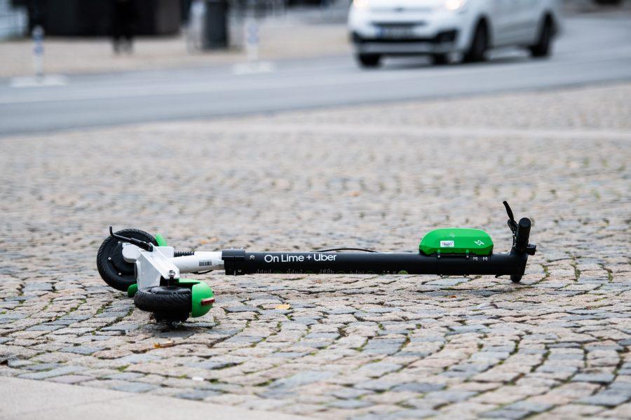 Elsparkcykel ligger slängd på trottoaren.