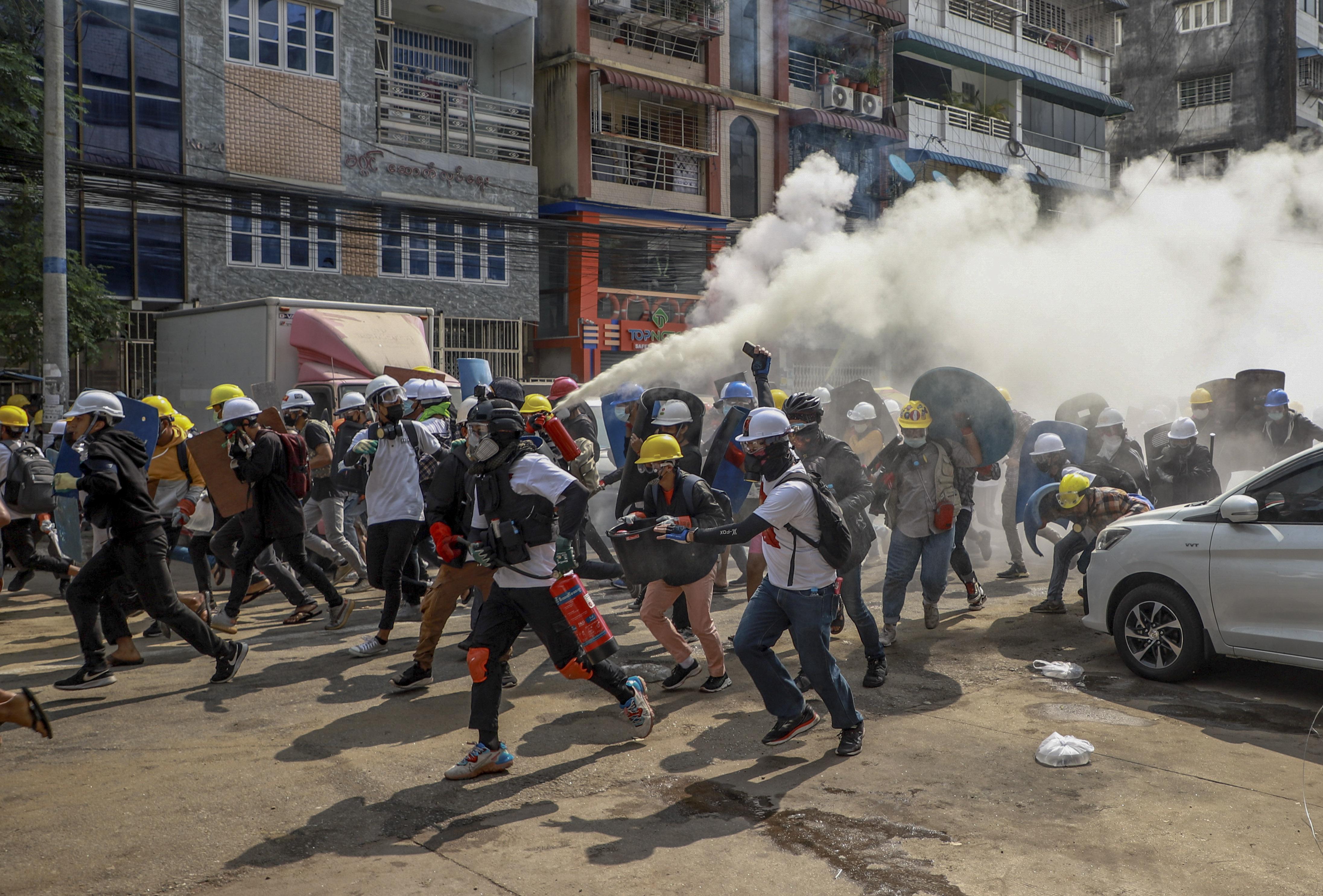 Demonstranter i Rangoon använder en brandsläckare mot militärens tårgas under onsdagens protester.