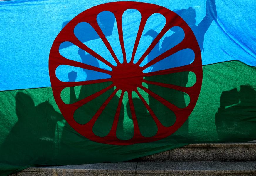 Den blå färgen i den romska flaggan representerar himlen, den gröna jorden och hjulet vandring.
