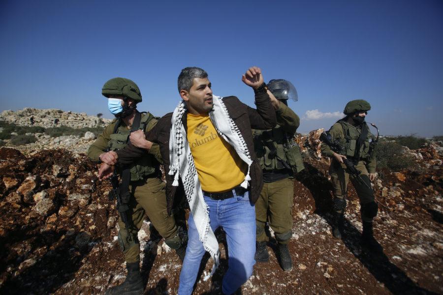 Israeliska soldater griper en palestinier som protesterar mot att en israelisk bosättning tar mer mark på Västbaken, Salfit, november 2020.