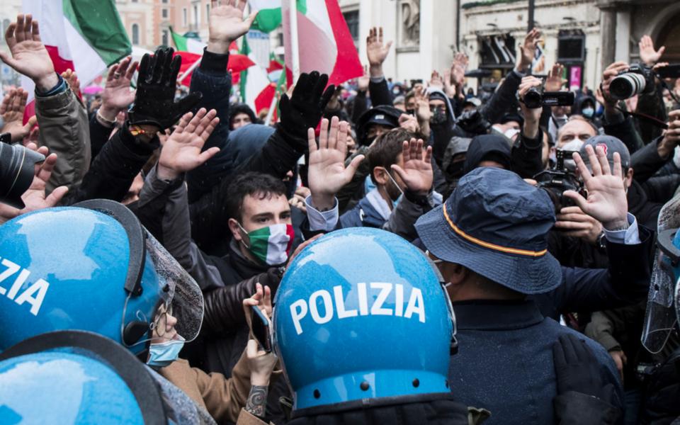 Kravallpolis agerar den 12 april mot demonstranter i Rom som kräver lättnader i de restriktioner som har införts på grund av coronapandemin.