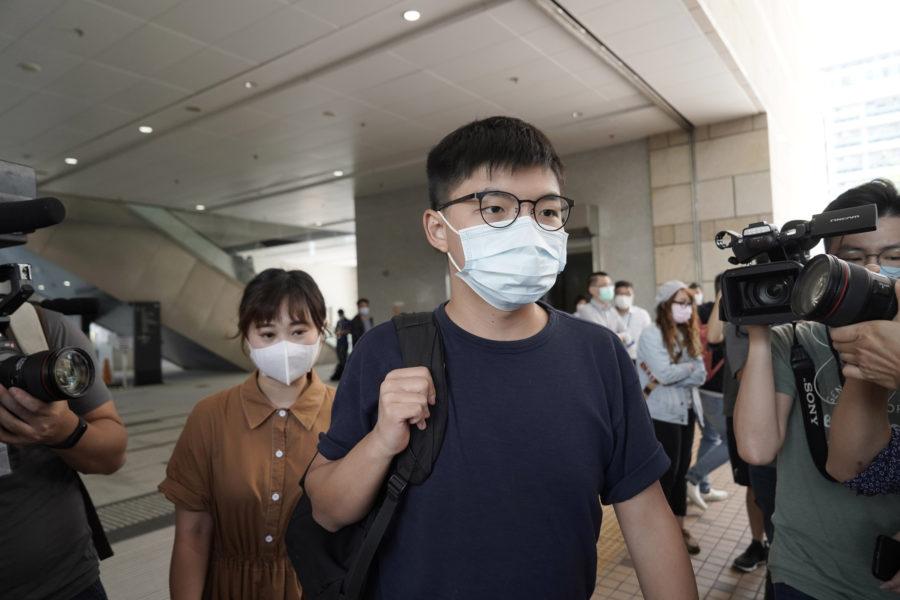 Aktivisten Joshua Wong, i mitten av bilden, tillsammans med aktivisten Tiffany Yuen Ka-wai, till vänster, på väg in till en rättegångsförhandling i Hongkong i oktober förra året.