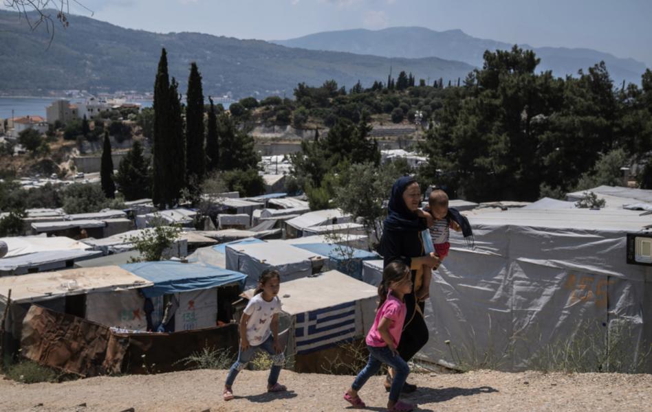 En kvinna från Afghanistan med sina tre barn i ett flyktingläger på Samos i Grekland.