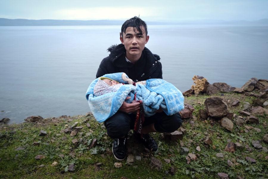 En flykting som just korsat egeiska havet håller i en bebis, som också var ombord på den lilla båten.