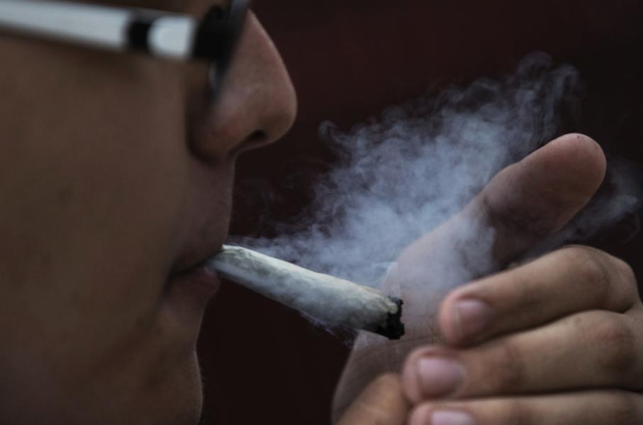 En man röker marijuana framför senatsbyggnaden i Mexico City.