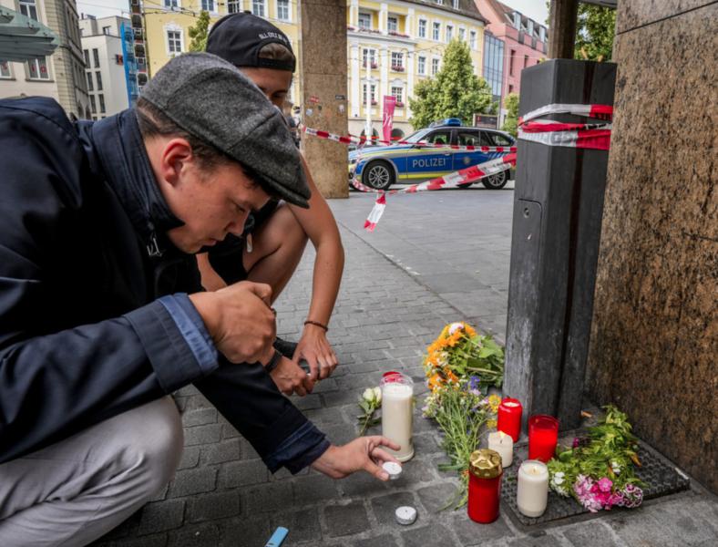 Blommor och ljus på brottsplatsen i Würzburg i Tyskland, där flera personer dödades i ett knivdåd i fredags.