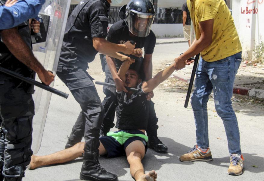 Tunisisk polis griper en demonstrant i huvudstaden Tunis.