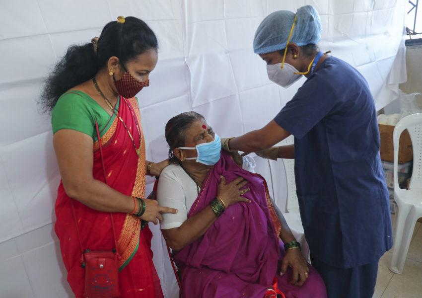 En äldre kvinna får coronavaccin på ett vaccinationscenter i Mumbai, Indien.