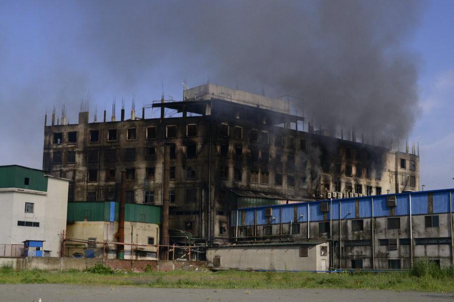 Rök stiger från den fabrik där en dödlig brand bröt ut utanför Dhaka, Bangladesh på fredagen.