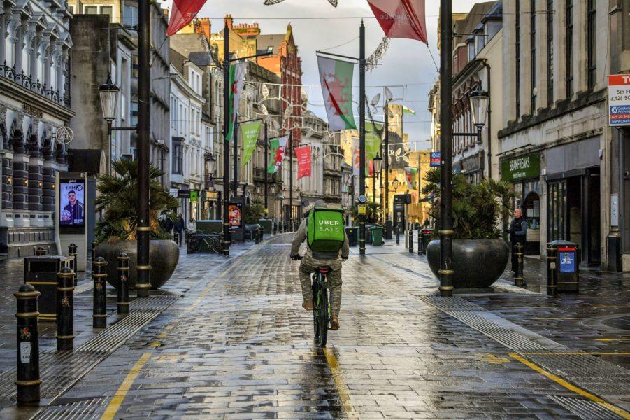 Ett matbud cyklar genom ett regnigt Cardiff i Wales.