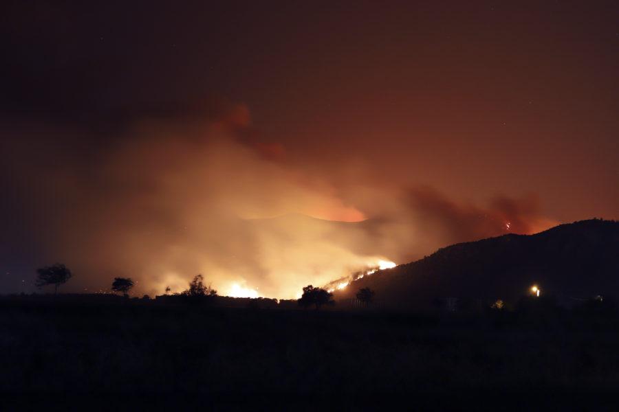 Röken ligger tät över kullarna och lågorna färgar natthimlen orange vid kraftverket Kemerkoy i Milas i sydvästra Turkiet.