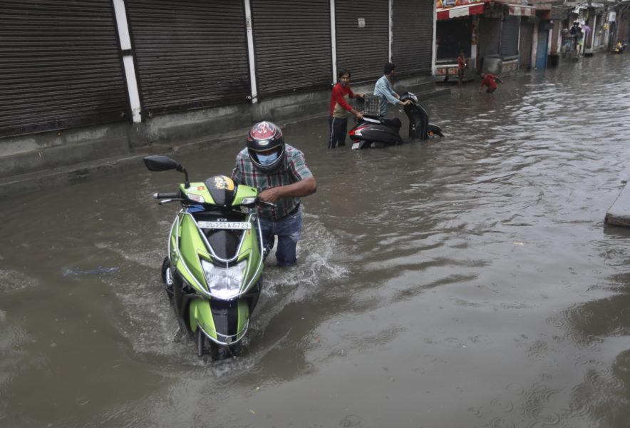 Delhibor kämpar sig fram genom den indiska huvudstadens vattenfyllda gator.